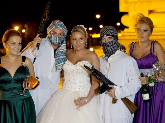 In this Sunday, Aug. 26, 2012 picture, a Romanian bride poses with mock kidnappers holding a toy weapons at the Triumph Arch in Bucharest, Romania. The arch, a replica of the Arc de Triomphe in Paris, the French capital, is a rendezvous place for brides on the wedding night for the bride stealing ritual. The ancient Romanian tradition of bride stealing is getting bigger, brasher and an increasingly common sight in the Romanian capital, the region's undisputed party town. (AP Photo/Vadim Ghirda)